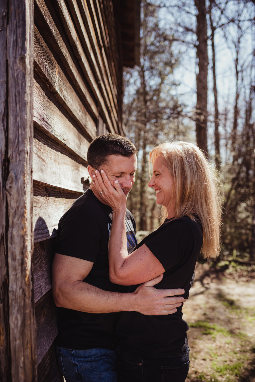 The couple snuggle each other on a barn in the morning light during their engagement session with Rose Trail Images in Wake Forest, NC.