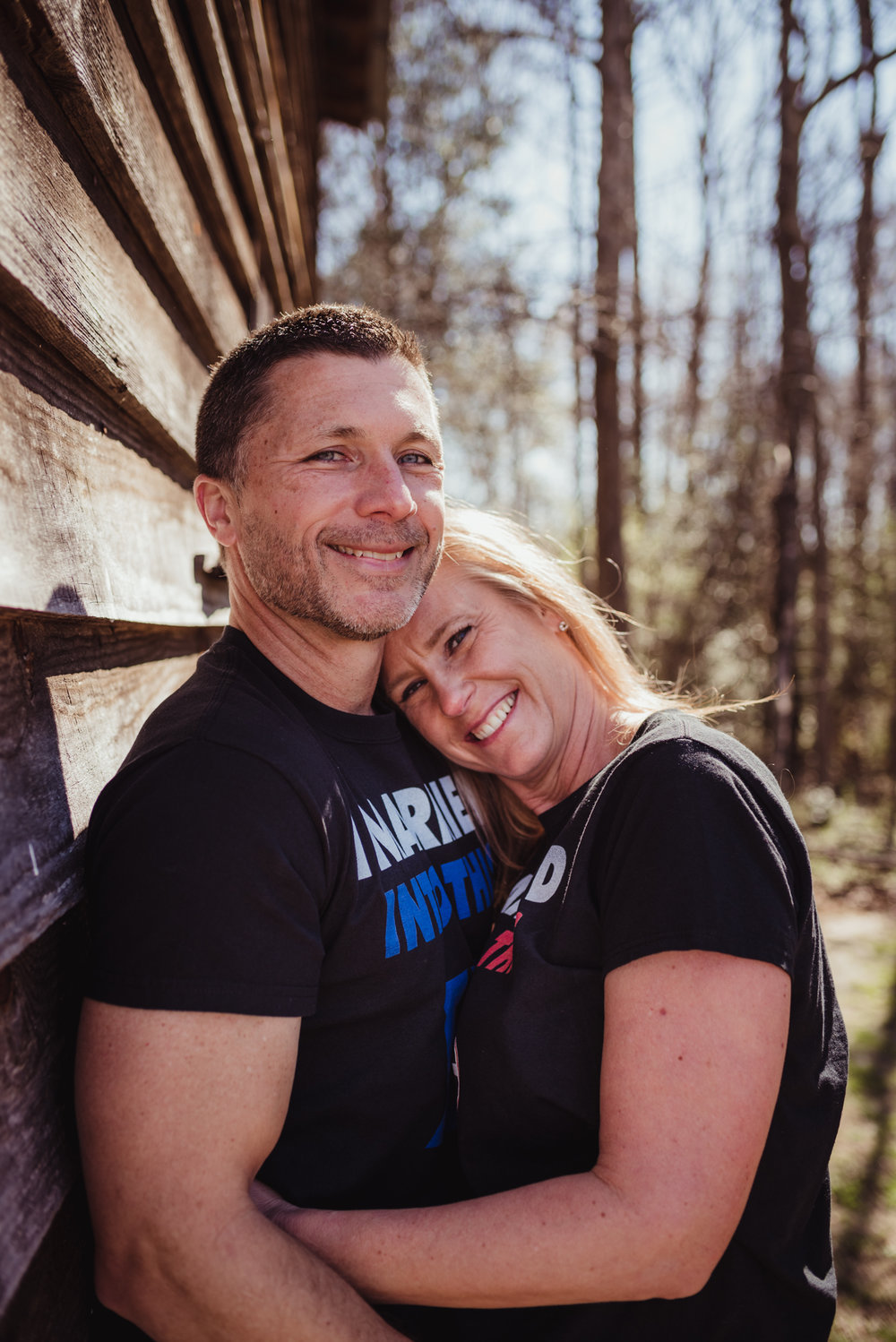 The couple pose for the camera at a barn in the morning light during their engagement session with Rose Trail Images in Wake Forest, NC.