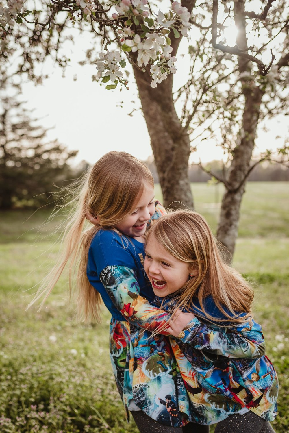 These sisters hugged and posed for Rose Trail Images during their family photo session in Wake Forest, North Carolina.