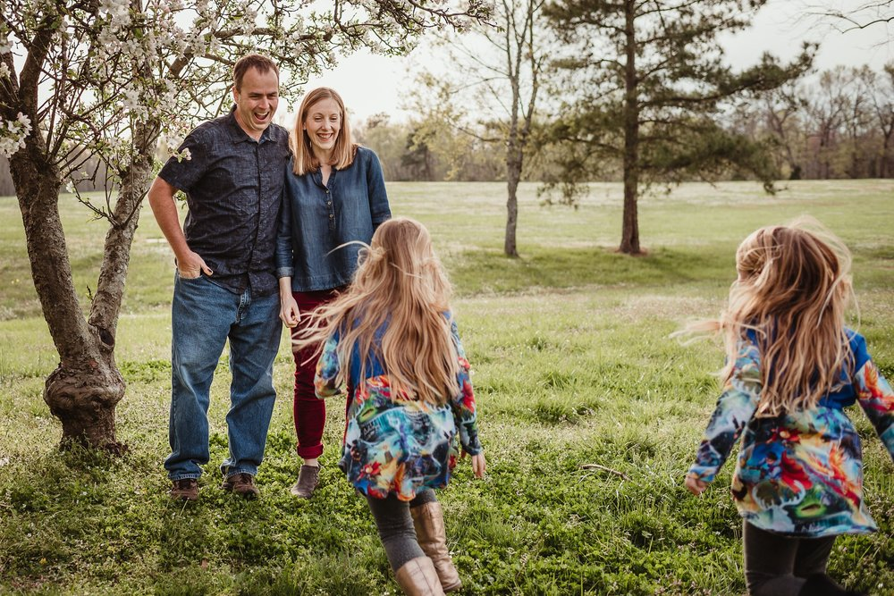 The daughters run to their parents during their family photo session with Rose Trail Images in Wake Forest, North Carolina.