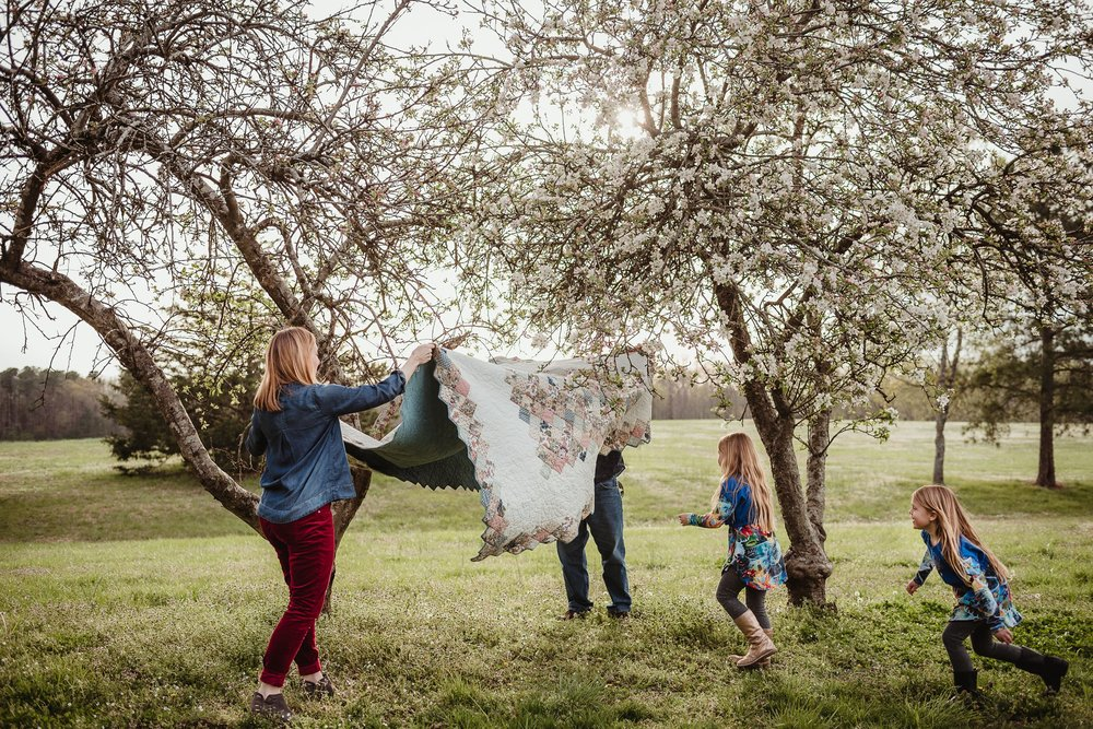 The parents get the quilt ready during their family photo session with Rose Trail Images in Wake Forest, North Carolina.