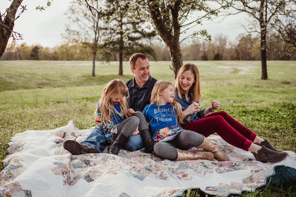The family of four share a laugh on the quilt during their family photo session with Rose Trail Images in Wake Forest, North Carolina.