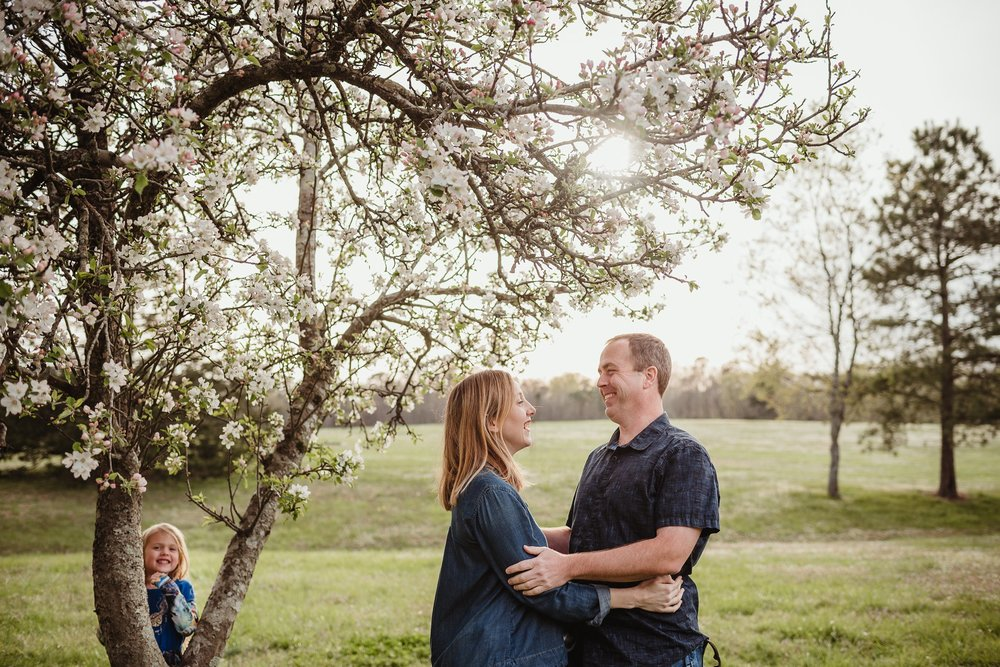 Mom and Dad got photobombed by their daughter during their family photo session with Rose Trail Images in Wake Forest, North Carolina.