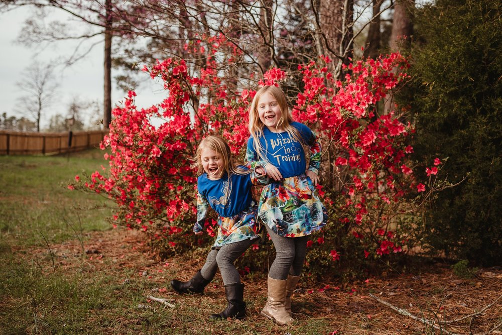 The sisters dance in front of the azaleas during their family photo session with Rose Trail Images in Wake Forest, North Carolina.