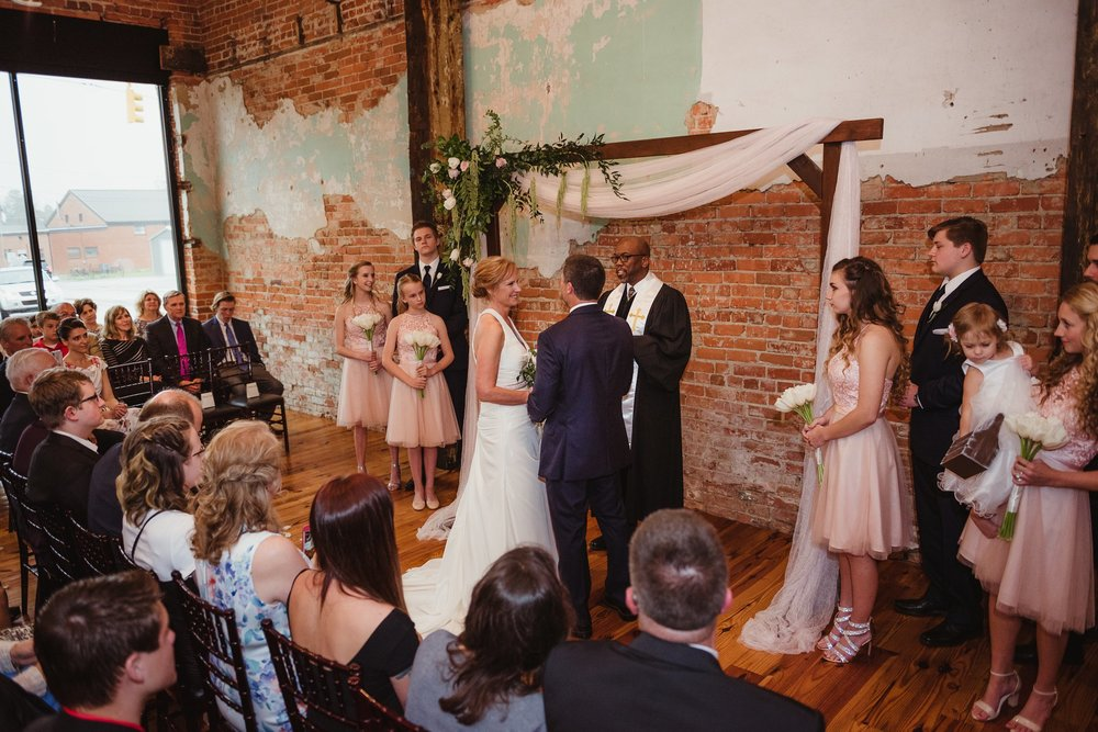 The bride and groom look at each other during their wedding ceremony at Cross and Main in Youngsville, NC, image taken by Rose Trail Images.