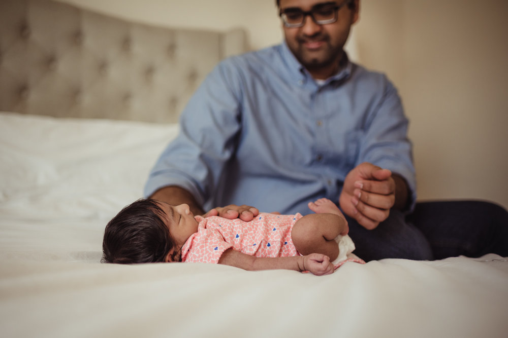 Dad calms down his new baby girl on his bed during their lifestyle newborn session with Rose Trail Images in Raleigh, North Carolina.