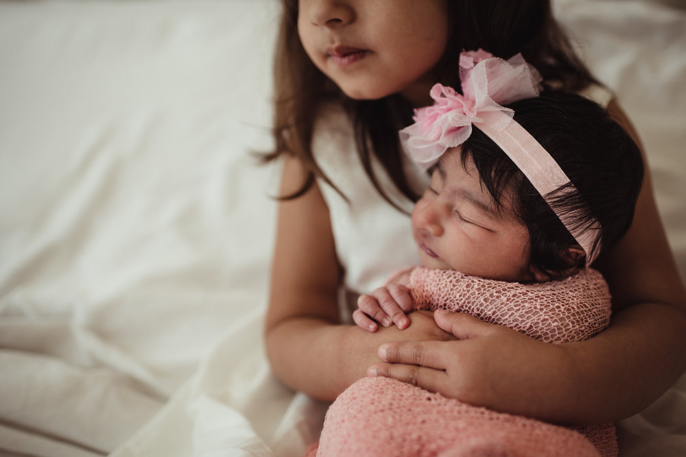 Older sister holds her new baby sister on their parents' bed during their lifestyle newborn session with Rose Trail Images in Raleigh, North Carolina.