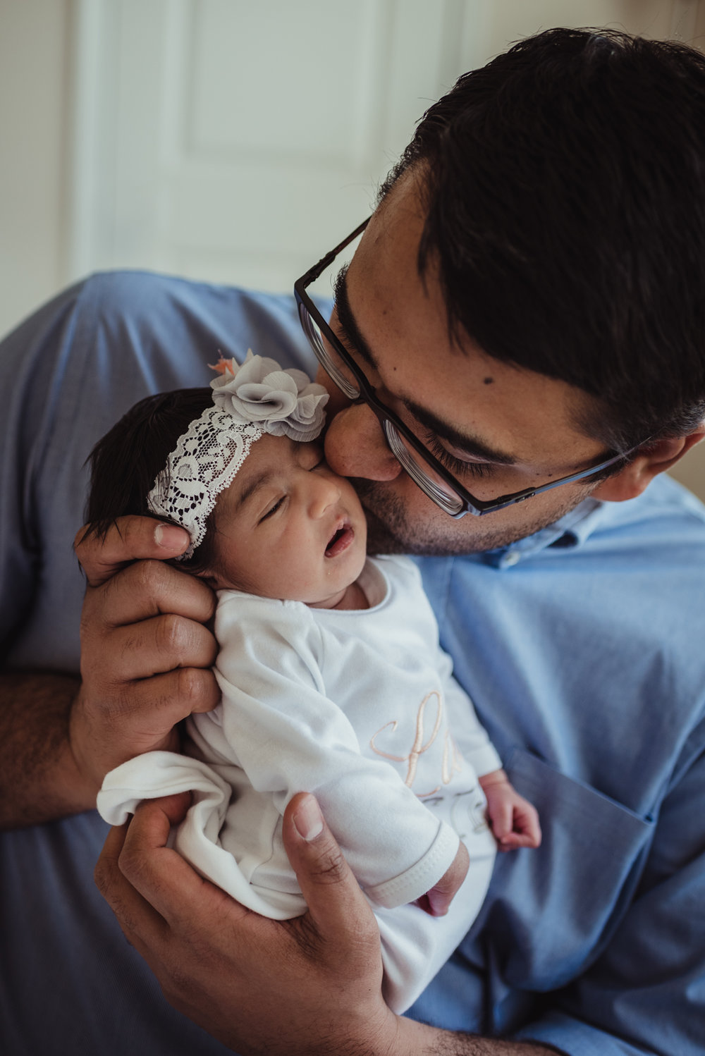 Dad kisses his newborn girl during their lifestyle newborn session with Rose Trail Images in Raleigh, North Carolina.