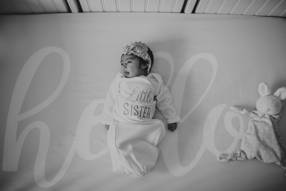 The newborn baby girl lay in her crib during her lifestyle newborn session with Rose Trail Images in Raleigh, North Carolina.