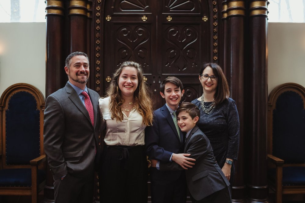 The bar mitzvah boy poses on the bema with his family for Rose Trail Images at Temple Beth Or in Raleigh, North Carolina.