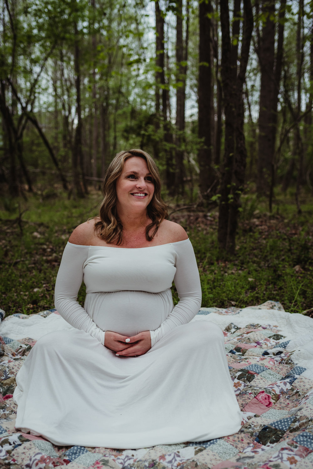 The pregnant Mama smiles for Rose Trail Images during her maternity shoot at Mill Bridge Nature Park in Rolesville, NC.
