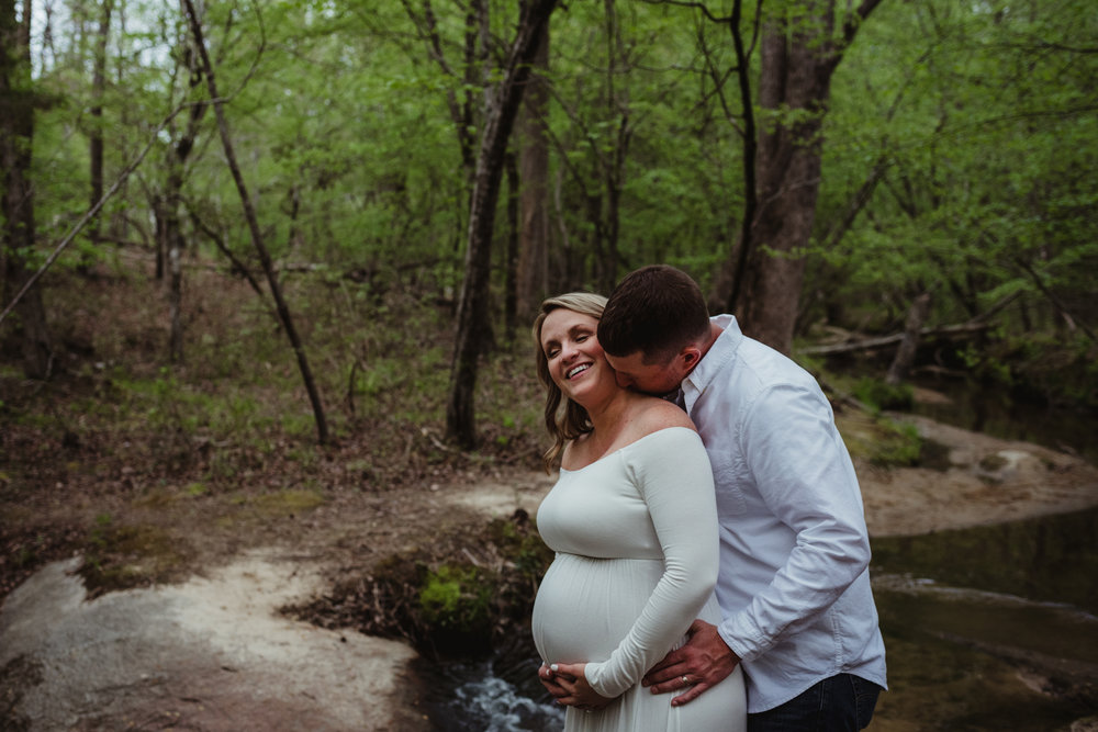 The soon to be parents get cuddly during their maternity shoot with Rose Trail Images at Mill Bridge Nature Park in Rolesville, NC.