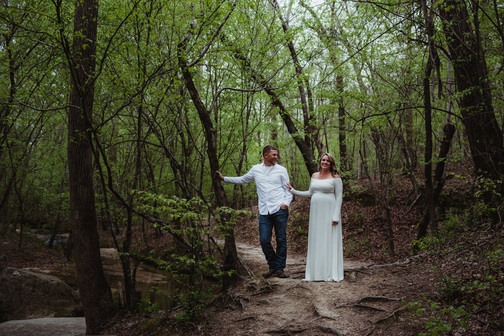 The soon to be parents laugh together on the trail during their maternity shoot with Rose Trail Images at Mill Bridge Nature Park in Rolesville, NC.