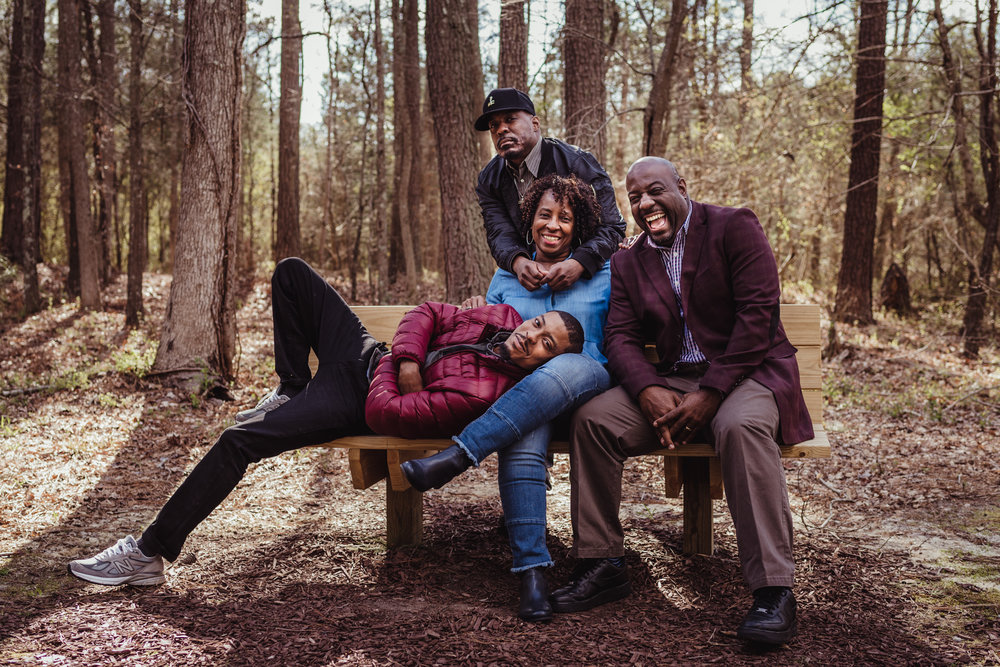 Mom poses for Rose Trail Images with her three adult sons on the bench in Rolesville Main Street Park.