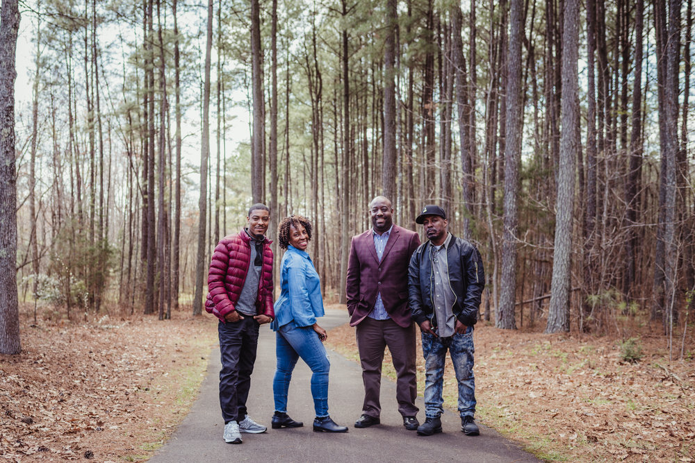 Mom poses on the trail for Rose Trail Images with her three adult sons in Rolesville Main Street Park.