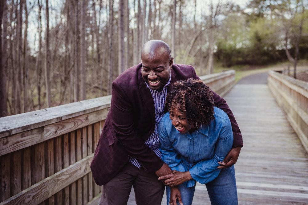 Mom laughs on the bridge with her oldest adult son in Rolesville Main Street Park during their family photo session with Rose Trail Images..