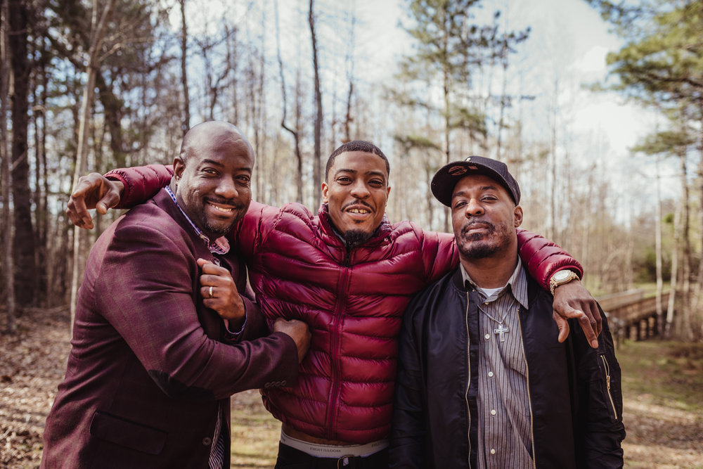The three adult sons pose on the bridge for Rose Trail Images during their family photo session in Rolesville Main Street Park.