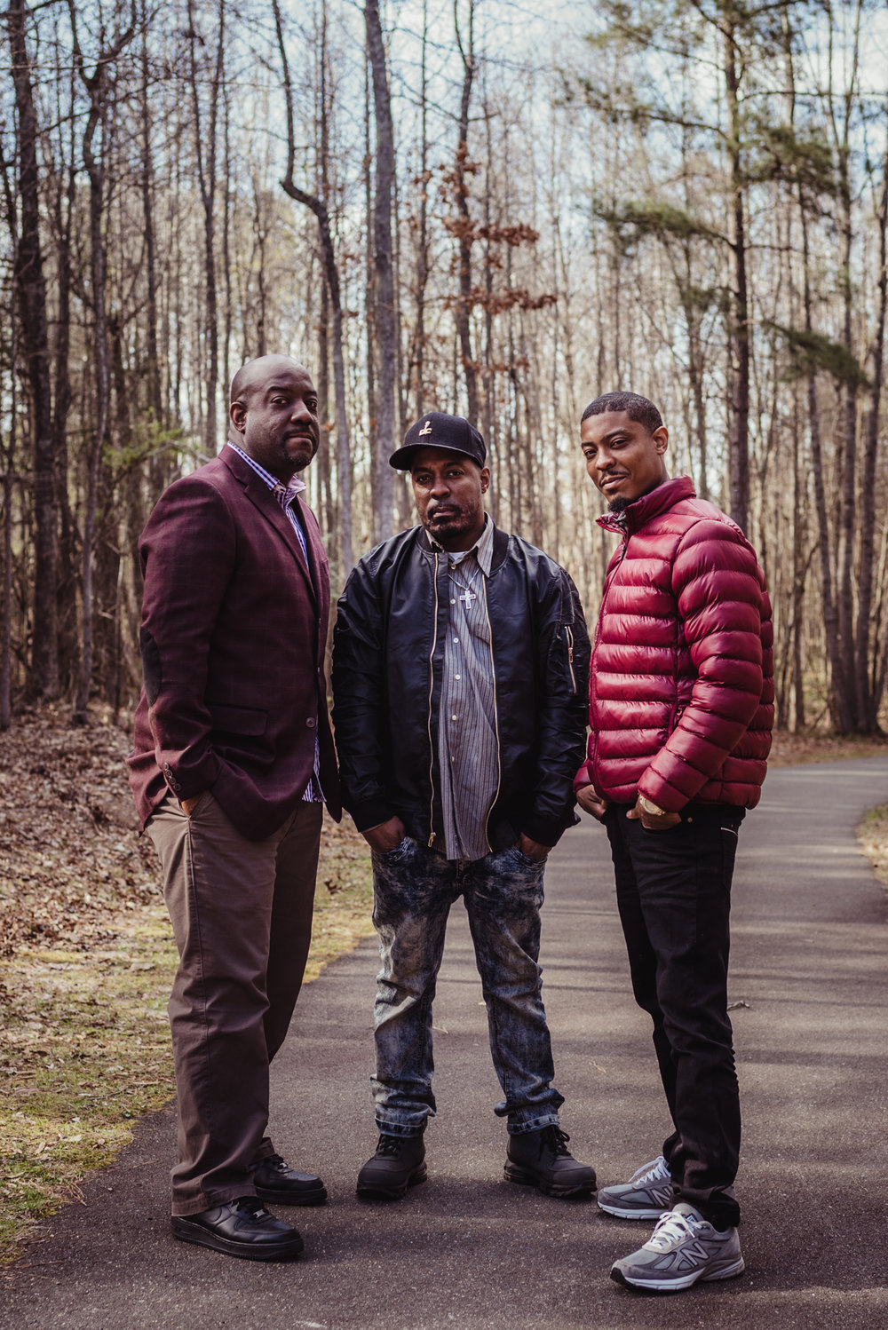The three adult sons pose on the trail for Rose Trail Images during their family photo session in Rolesville Main Street Park.