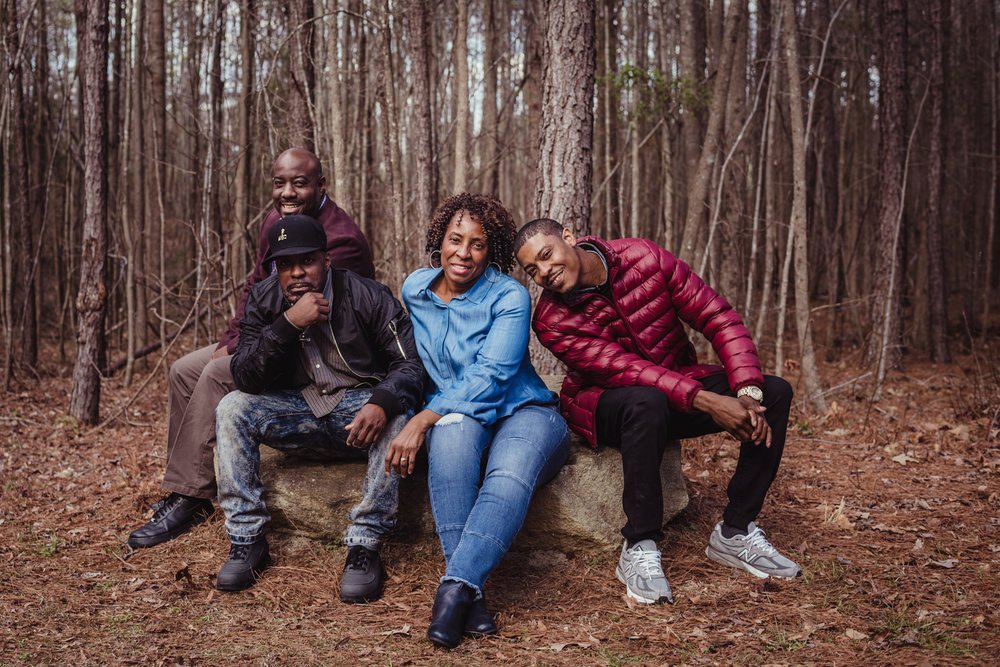 The three adult sons pose on the rock next to their Mom for Rose Trail Images during their family photo session in Rolesville Main Street Park.