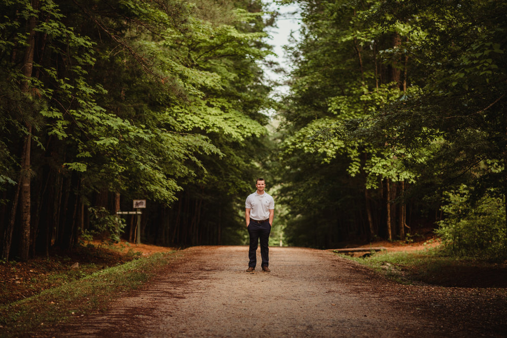 Harrison, walking down the dirt path, had his senior portraits done at Durant Nature Preserve in Raleigh, NC by Rose Trail Images.