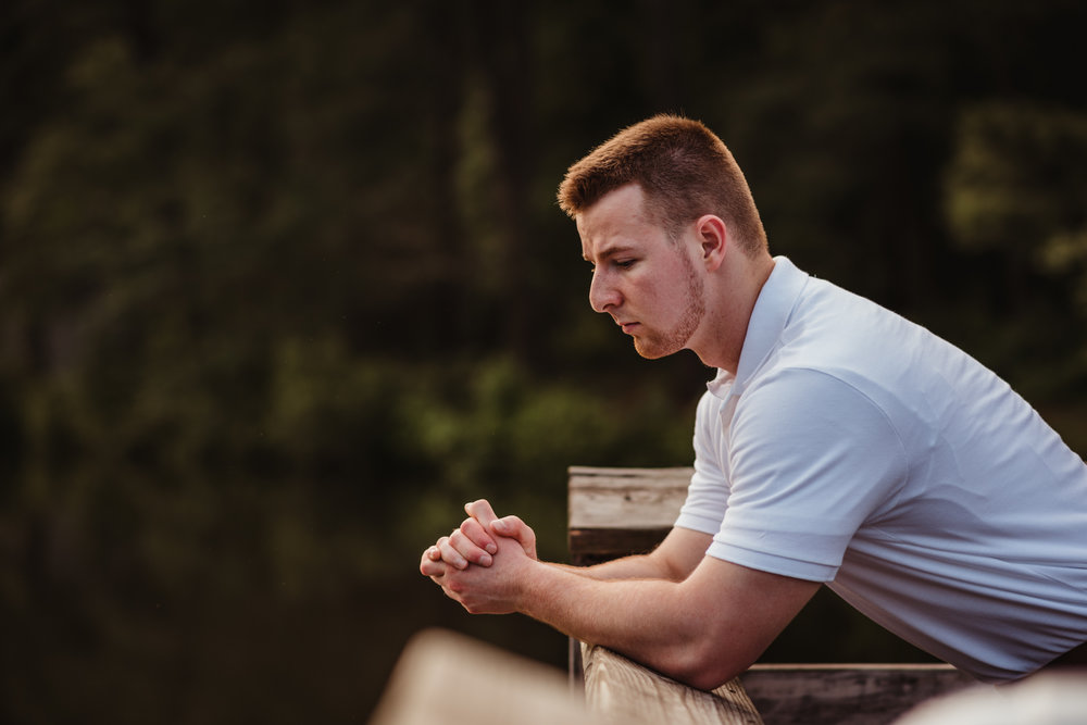 Harrison leans over the dock during his senior portraits at Durant Nature Preserve in Raleigh, NC by Rose Trail Images.