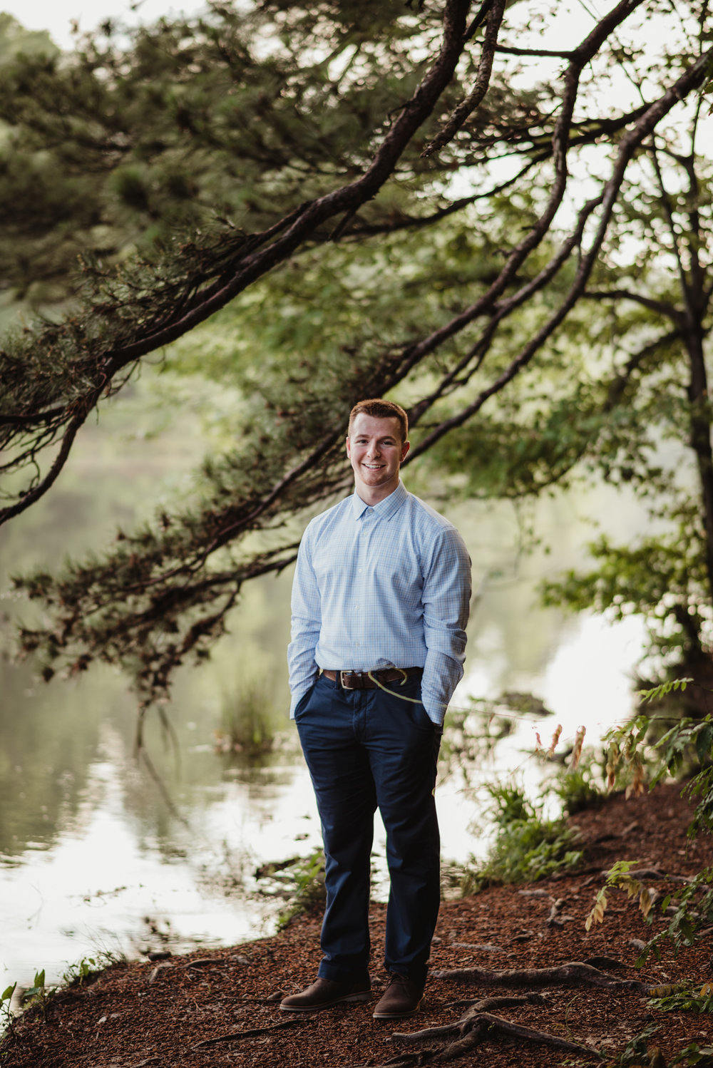 Harrison smiled by the lake for Rose Trail Images during his senior portraits in the woods at Durant Nature Preserve in Raleigh, NC.