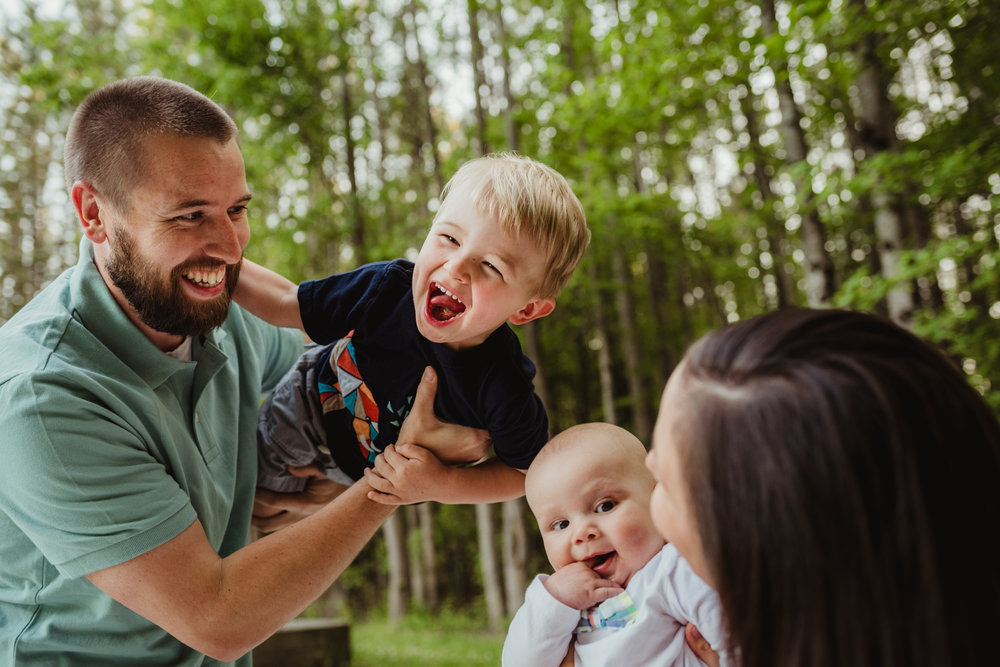 This family of four laughs during their photo session with Rose Trail Images in Rolesville, North Carolina.