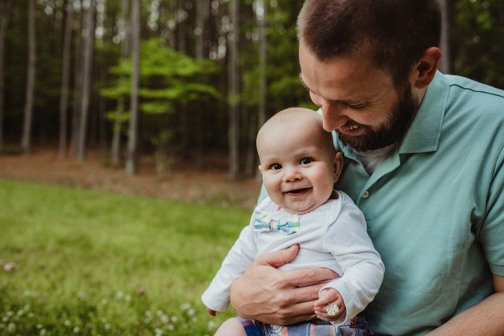 This happy baby smiles with daddy during their photo session with Rose Trail Images in Rolesville, North Carolina.