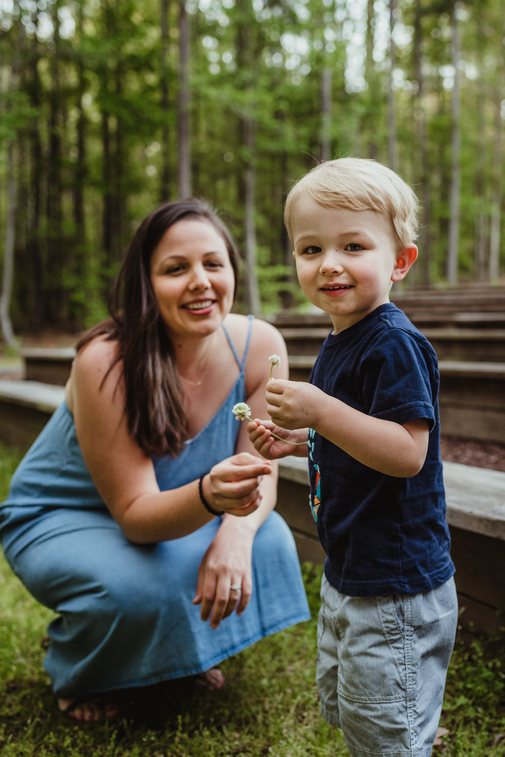 The little boy gives flowers to his mom during their family photo session with Rose Trail Images in Rolesville, North Carolina.