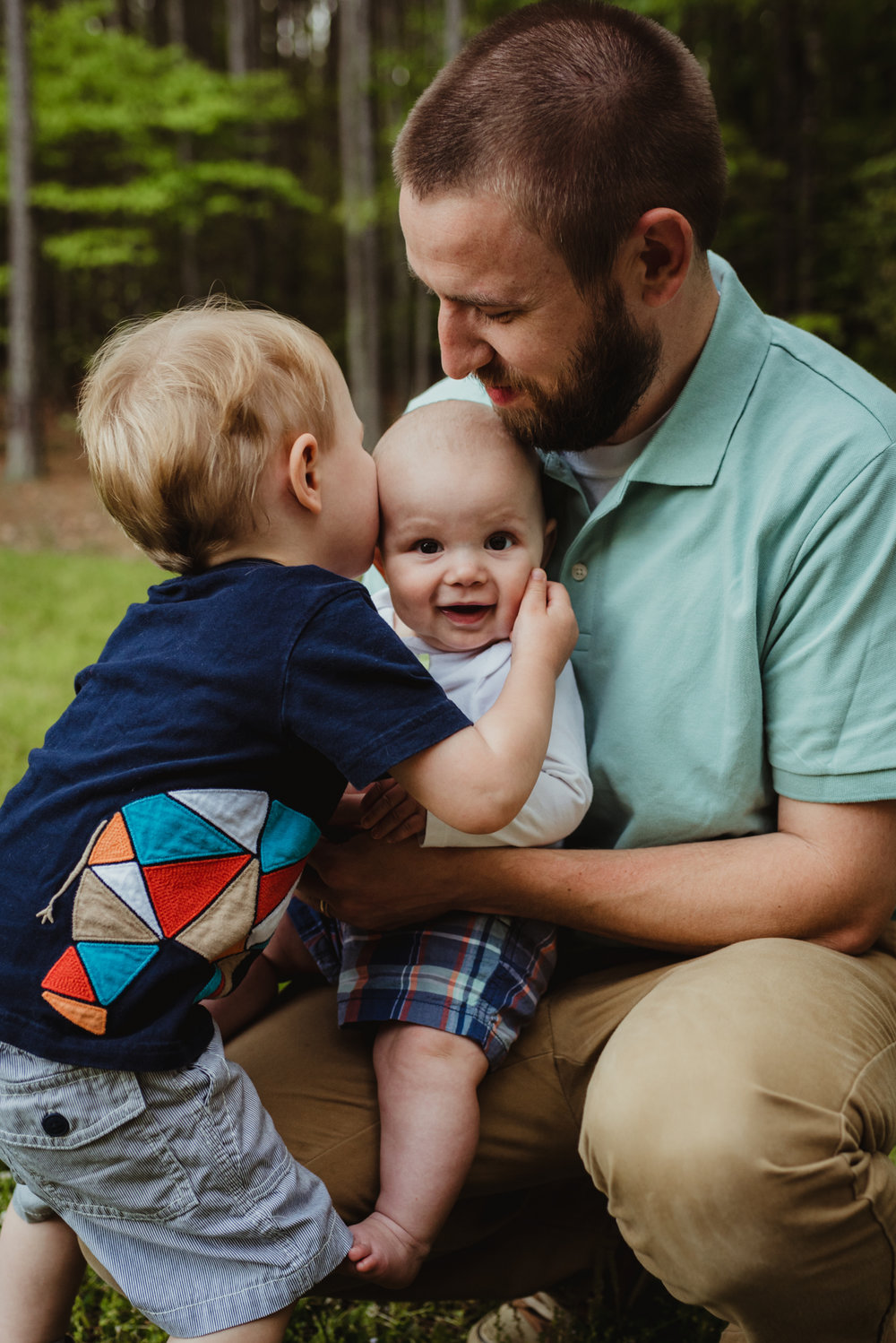 This big brother kisses his baby brother during their photo session with Rose Trail Images in Rolesville, North Carolina.