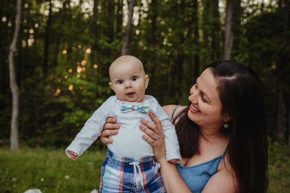 Baby stares at the camera with Mommy holding him during their photo session with Rose Trail Images in Rolesville, North Carolina.