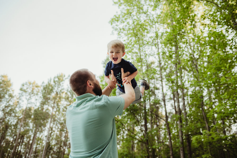 Daddy tosses big brother into the air during their photo session with Rose Trail Images in Rolesville, North Carolina.