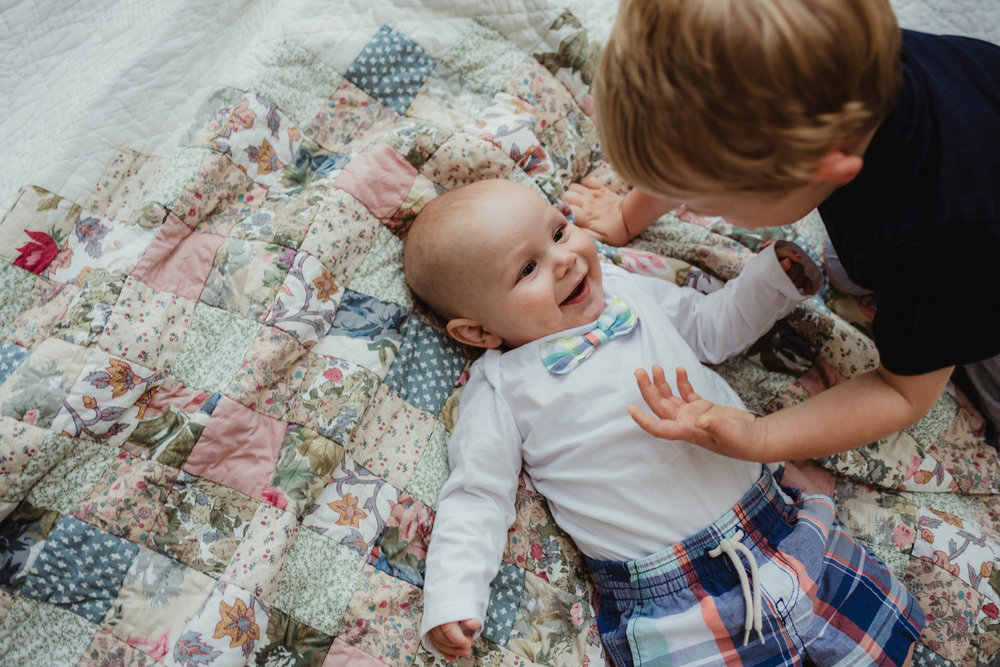 Big brother plays with little brother on a quilt during their photo session with Rose Trail Images in Rolesville, North Carolina.