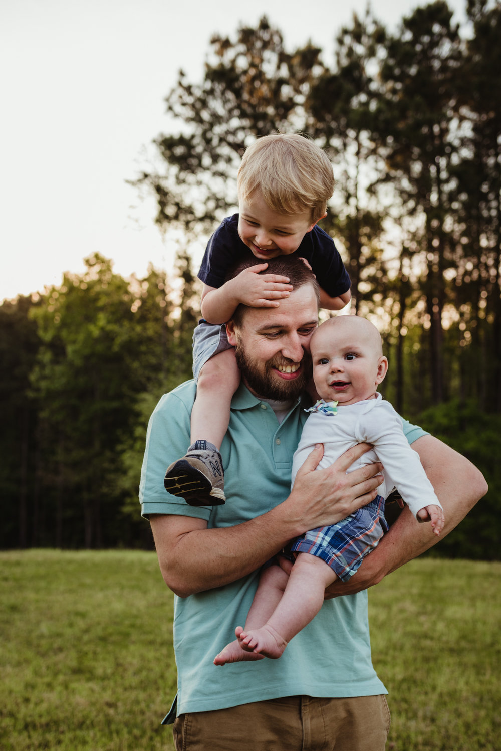 Daddy holds onto baby brother and big brother during their photo session with Rose Trail Images in Rolesville, North Carolina.