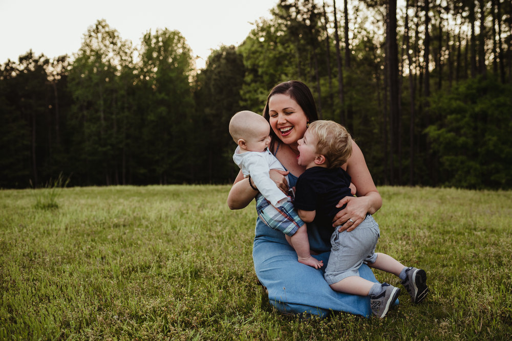 Mommy plays with baby brother and big brother during their family's photo session with Rose Trail Images in Rolesville, North Carolina.