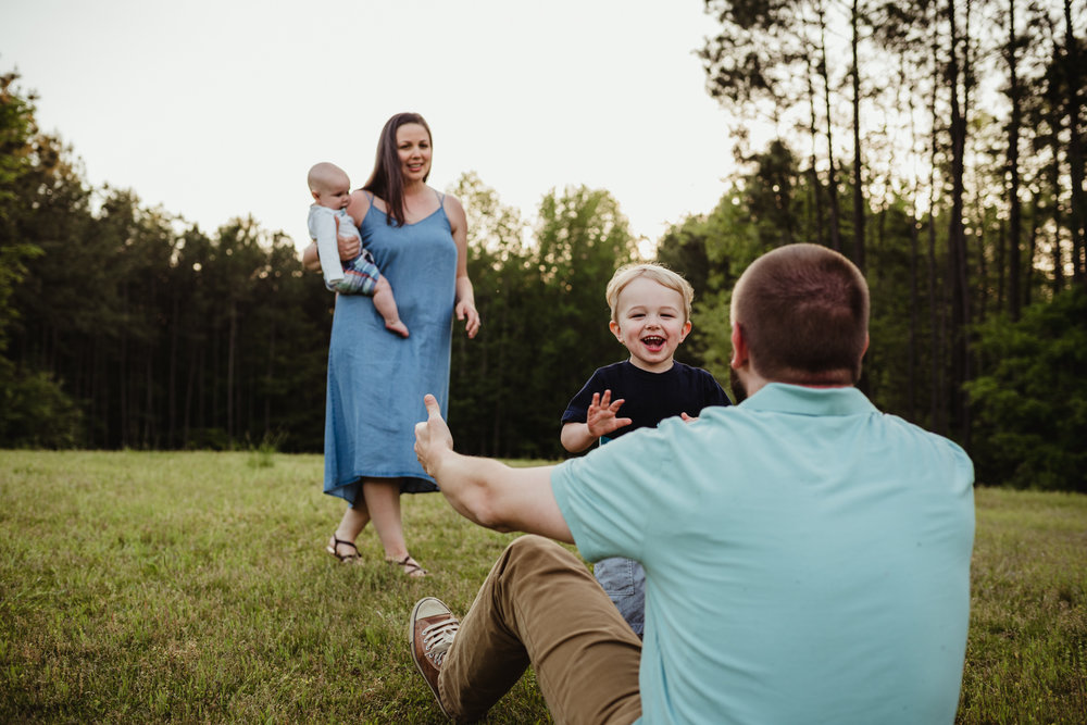 Older brother runs and tackles Daddy during their family photo session with Rose Trail Images in Rolesville, North Carolina.