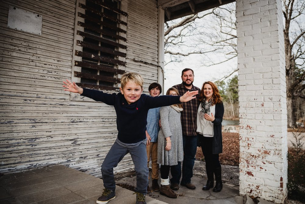 This family of five stood in front of an abandoned store front at Lake Myra in Wendell, NC for their family pictures with Rose Trail Images.
