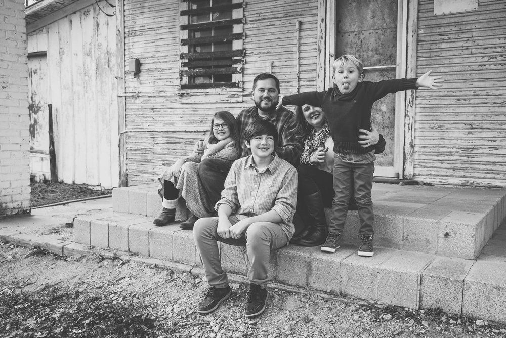 This family of five sat in front of an abandoned store front at Lake Myra in Wendell, NC for their family pictures with Rose Trail Images.