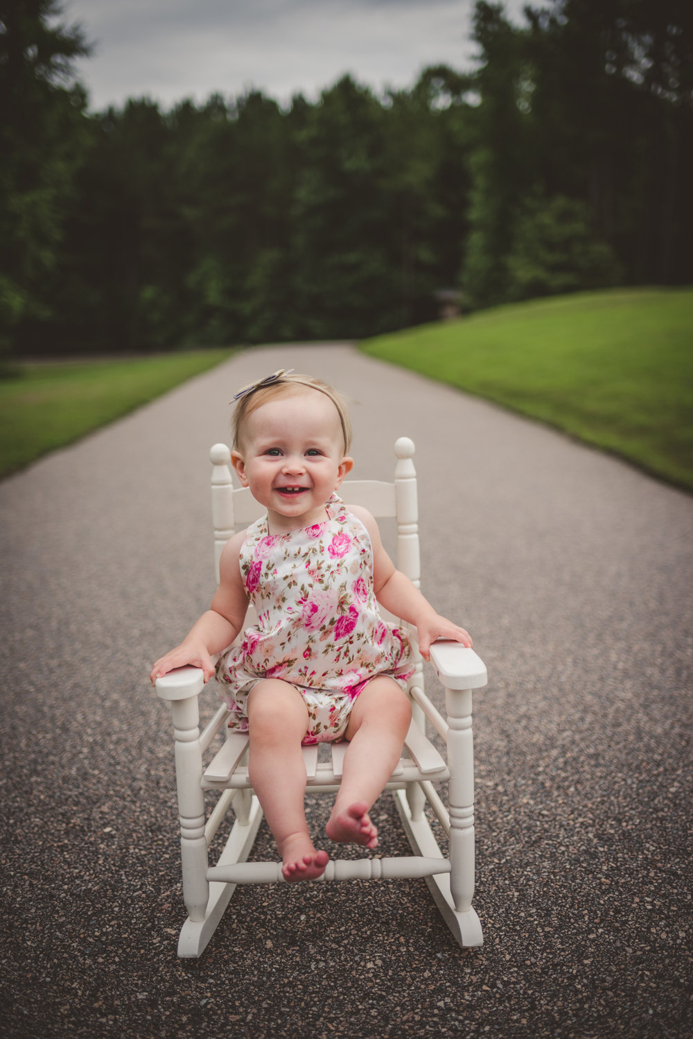 This little girl is smiling while sitting in an old rocking chair for her first birthday in Rolesville, North Carolina, image taken by Rose Trail Images.