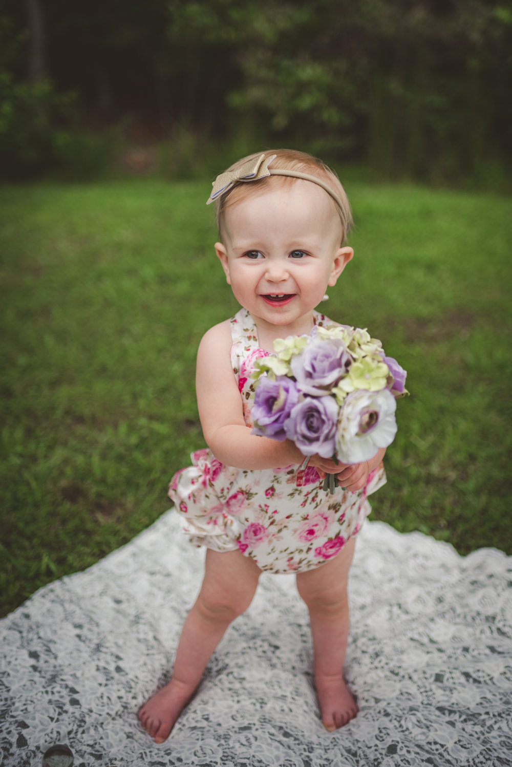 This little girl holds a bouquet of flowers for her first birthday in Rolesville, North Carolina, image taken by Rose Trail Images.