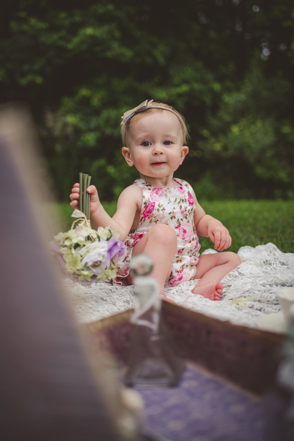 This little one year old girl is sitting with vintage props from her parents wedding in Rolesville, North Carolina, image taken by Rose Trail Images.