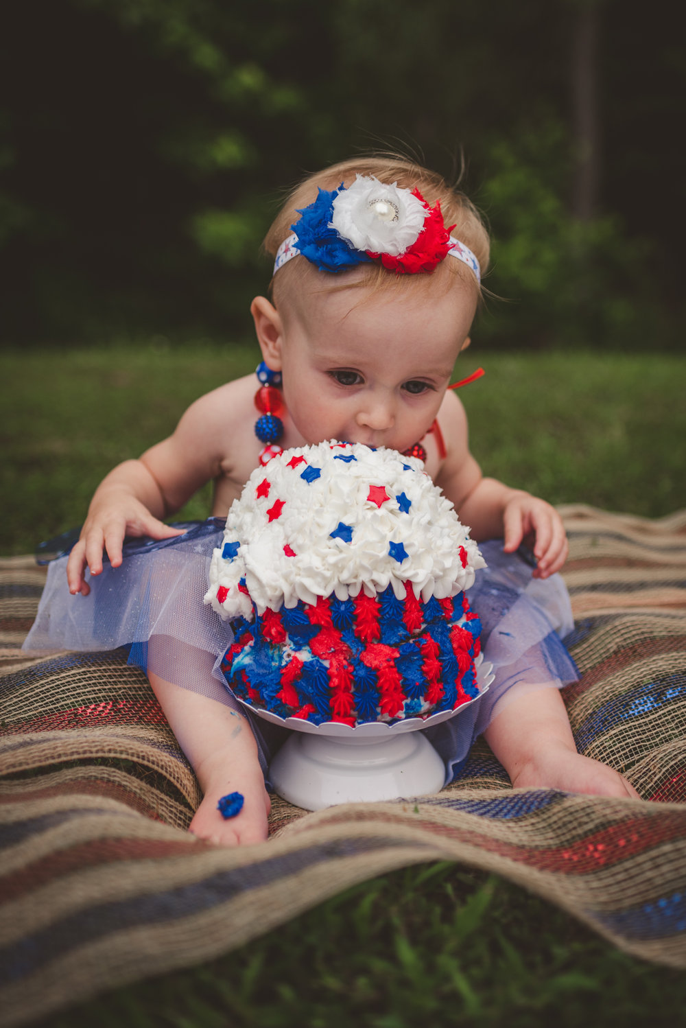 This little girl eats cake for the first time for her one year old fourth of July cake smash session with Rose Trail Images in Rolesville, North Carolina.