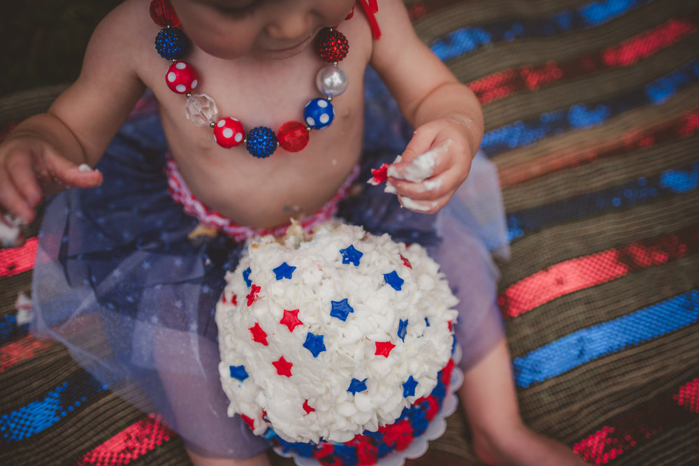 This little girl is eating her red, white and blue cake for her one year old fourth of July cake smash session with Rose Trail Images in Rolesville, North Carolina.