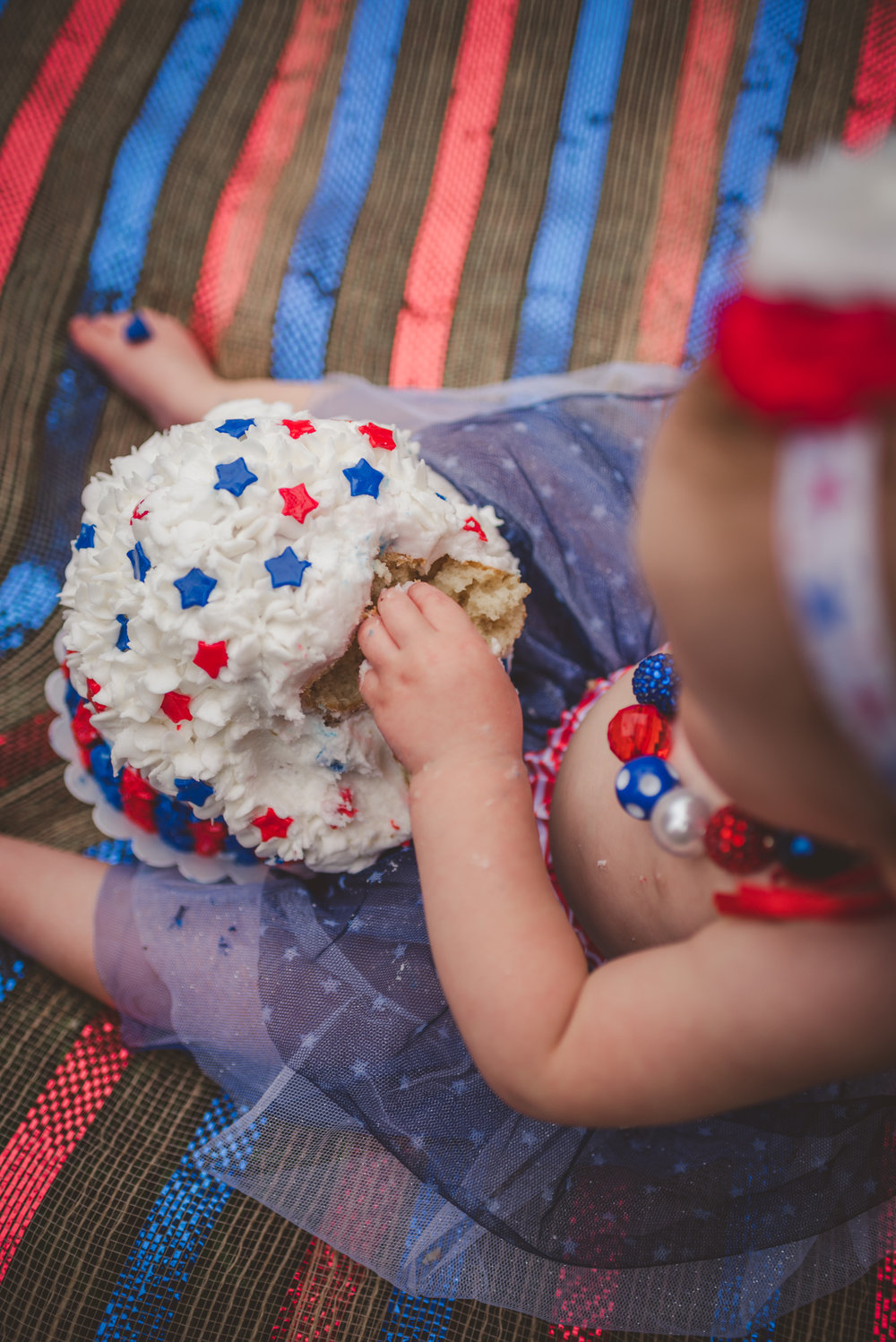 This little girl sticks her fingers in her red, white, and blue cake for her one year old fourth of July cake smash session with Rose Trail Images in Rolesville, North Carolina.