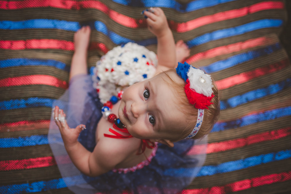 This little girl looks up from her cake for her one year old fourth of July cake smash session with Rose Trail Images in Rolesville, North Carolina.