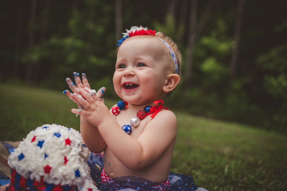 This little girl claps while eating red, white, and blue cake for her one year old fourth of July cake smash session with Rose Trail Images in Rolesville, North Carolina.