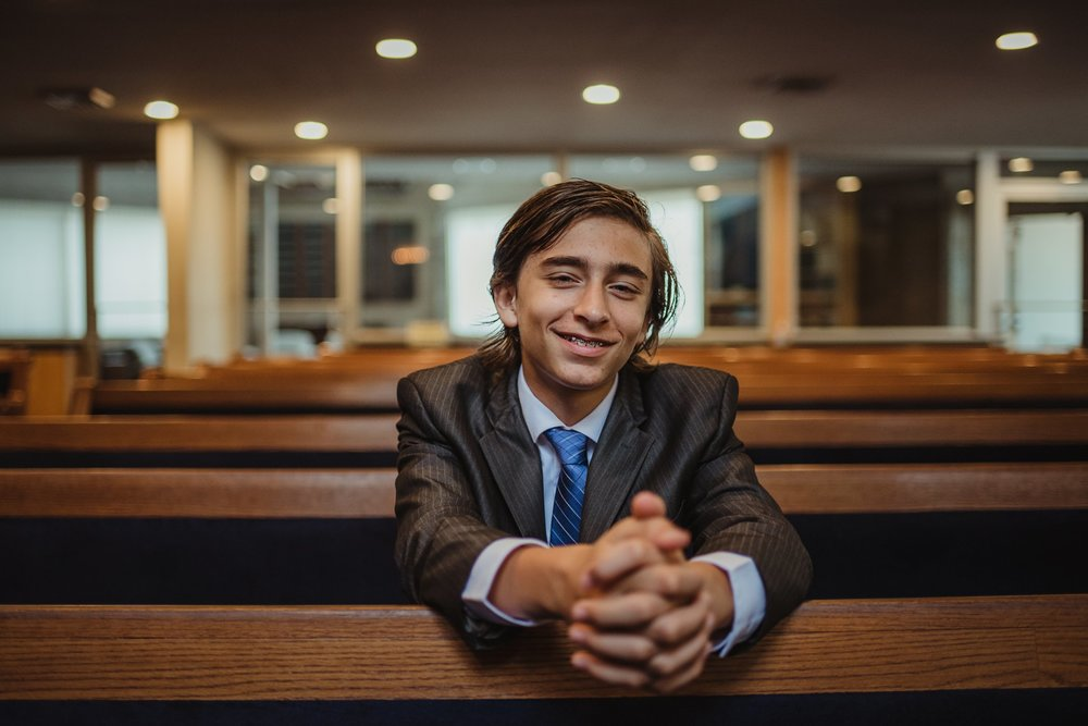 The bar mitzvah boy poses in a pew for Rose Trail Images at Temple Beth Or in Raleigh, North Carolina.