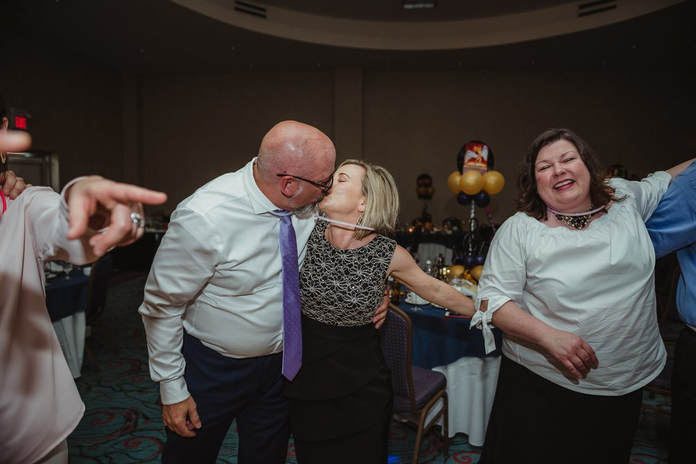 The parents of the Mitzvah boy kissed during Joel's mitzvah celebration party at Embassy Suites in Raleigh, North Carolina, images by Rose Trail Images.