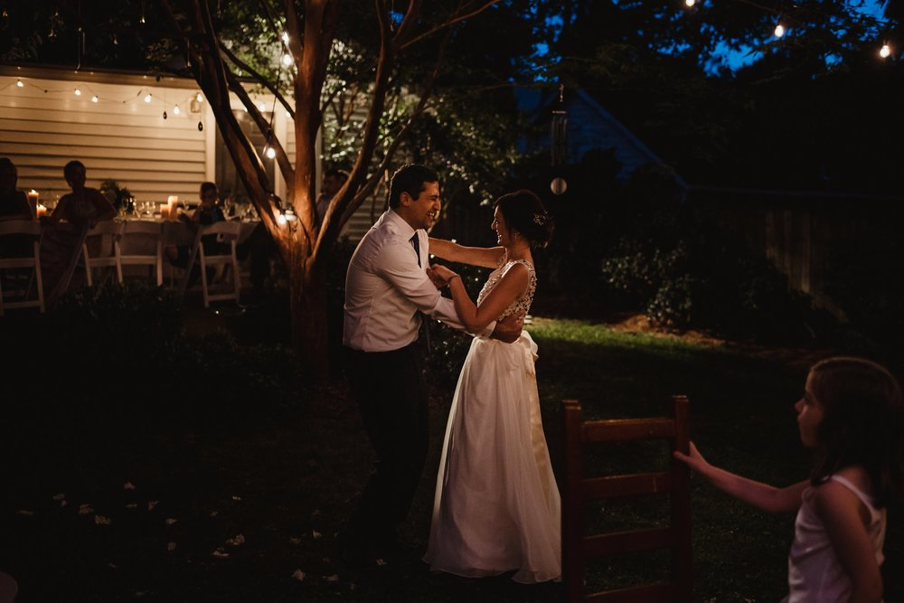 The bride and groom had their first dance under the market lights at their home in Raleigh for their intimate wedding, pictures by Rose Trail Images.