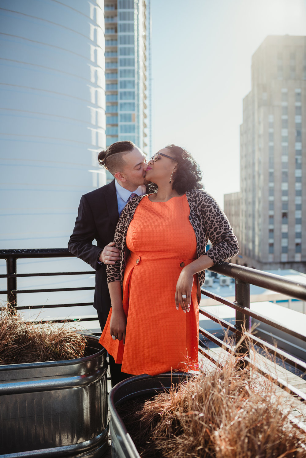 The husband and wife kiss for a picture by Rose Trail Images on the rooftop of the Durham Hotel in Durham, North Carolina.
